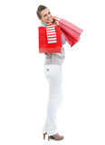 Happy young woman in sweater holding christmas shopping bags Stock Photo