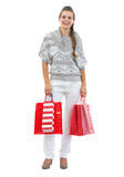 Happy young woman in sweater holding christmas shopping bags Royalty Free Stock Photo