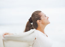 Happy young woman in sweater on lonely beach rejoicing Royalty Free Stock Photos