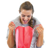 Happy young woman in sweater looking in shopping bag Stock Photo
