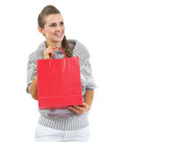 Happy young woman in sweater with red christmas shopping bag Royalty Free Stock Photography