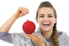 Happy young woman in sweater showing christmas ball Stock Photos