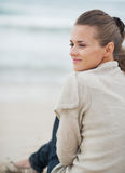 Happy young woman in sweater sitting on lonely beach Royalty Free Stock Images