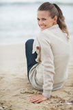 Happy young woman in sweater sitting on lonely beach Royalty Free Stock Image