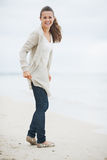 Happy young woman in sweater walking on lonely beach Stock Photography