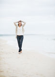 Happy young woman in sweater walking on lonely beach Stock Photo