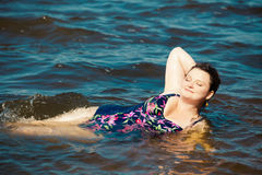 Happy young woman in swim suite laying on rock.  Sea shore Stock Image