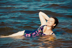 Happy young woman in swim suite laying on rock.  Sea shore Stock Photos