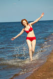 Happy young woman in swim suite laying on rock.  Sea shore Stock Photo