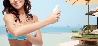 Happy young woman in swimsuit applying sunscreen Royalty Free Stock Photo