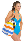 Happy young woman in swimsuit with beach bag Stock Photo