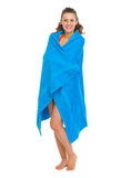 Happy young woman in swimsuit bundle up in towel Stock Images