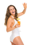 Happy woman in swimsuit with cocktail saluting Royalty Free Stock Images