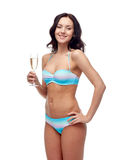 Happy young woman in swimsuit drinking champagne Stock Photo