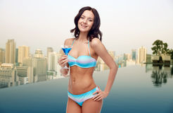 Happy young woman in swimsuit drinking cocktail Stock Photography