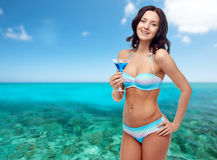 Happy young woman in swimsuit drinking cocktail Stock Photo