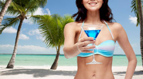 Happy young woman in swimsuit drinking cocktail Stock Photos