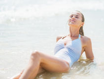 Happy young woman in swimsuit enjoying laying in sea water Stock Photo