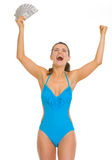 Happy young woman in swimsuit with fan of dollars Stock Photo