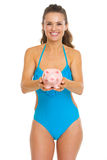 Happy young woman in swimsuit giving piggy bank Stock Photo