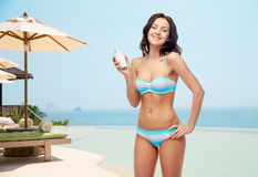 Happy young woman in swimsuit holding sunscreen Stock Photos