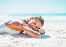 Happy young woman in swimsuit laying on sandy beach Royalty Free Stock Images