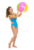 Happy young woman in swimsuit playing with beach ball. Full length portrait of happy young woman in swimsuit playing with beach ball isolated on white Stock Photography