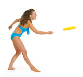 Happy young woman in swimsuit playing with frisbee Stock Images
