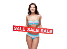 Happy young woman in swimsuit with red sale sign Royalty Free Stock Images