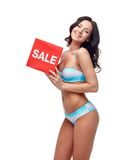 Happy young woman in swimsuit with red sale sign Royalty Free Stock Photo
