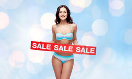Happy young woman in swimsuit with red sale sign Stock Photos