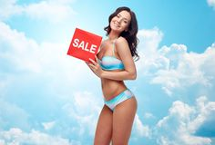 Happy young woman in swimsuit with red sale sign Royalty Free Stock Image