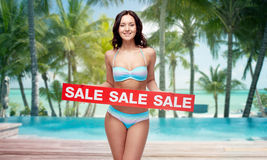 Happy young woman in swimsuit with red sale sign. People, summer, travel and tourism concept - happy young woman in bikini swimsuit with red sale sign over Stock Image