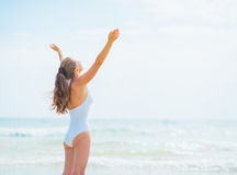 Happy young woman in swimsuit rejoicing on sea shore Royalty Free Stock Photography
