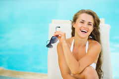 Happy young woman in swimsuit relaxing poolside. Portrait of happy young woman in swimsuit relaxing poolside Stock Image