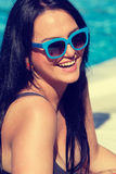 Happy young woman in swimsuit relaxing poolside Stock Image