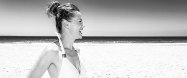 Happy young woman in swimsuit on seashore looking into distance Royalty Free Stock Image