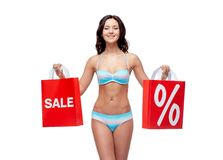 Happy young woman in swimsuit with shopping bags. People, fashion, swimwear, summer sale and beach concept - happy young woman in bikini swimsuit with red Stock Photos