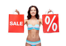 Happy young woman in swimsuit with shopping bags. People, fashion, swimwear, summer sale and beach concept - happy young woman in bikini swimsuit with red Stock Images