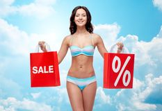Happy young woman in swimsuit with shopping bags. People, fashion, swimwear, summer sale and beach concept - happy young woman in bikini swimsuit with red Royalty Free Stock Image