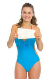 Happy young woman in swimsuit showing air tickets Royalty Free Stock Image