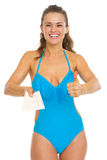 Happy young woman in swimsuit showing air tickets and thumbs up Royalty Free Stock Photo