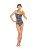 Happy young woman in swimsuit showing bo. Full length portrait of happy young woman in swimsuit showing bottle of sun block creme Stock Photos