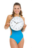 Happy young woman in swimsuit showing clock Royalty Free Stock Photography