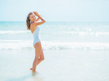 Happy young woman in swimsuit standing at seaside Stock Photography