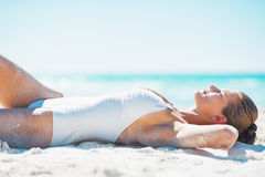 Happy young woman in swimsuit tanning on beach. Happy young woman in white  swimsuit tanning on sandy  beach Royalty Free Stock Photography
