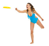 Happy young woman in swimsuit throwing flying disc Royalty Free Stock Photography