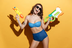 Happy young woman in swimwear holding toys water gun Royalty Free Stock Image