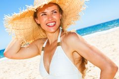 Happy young woman in swimwear on seacoast looking aside Stock Image