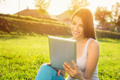 Happy young woman with tablet in park on sunny summer day Stock Photos